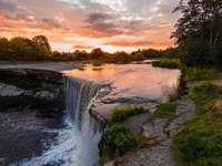 Solnedgång - En sikt av inställningssolen över vattenfallet