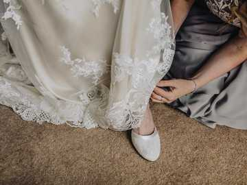 woman fixing shoes of another woman - Bridesmaids helping Bride get ready for wedding.