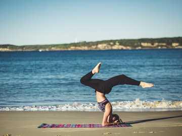 Yoga sull'oceano - donna che fa yoga in riva al mare.