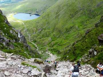 La scala del diavolo - persone che camminano sulla strada rocciosa vicino a montagne verdi durante il giorno. Carrauntoohil