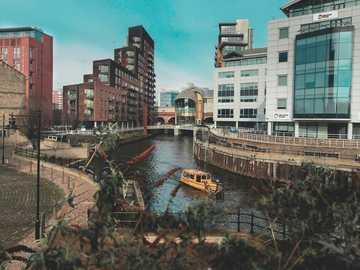 beige Boot auf Gewässer zwischen Gebäuden - River Aire am Granary Wharf mit Blick auf die ne. Leeds, Großbritannien