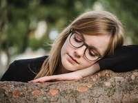 Thoughtful - tilt shift photography of woman sleeping on log. Park Café Kleine Schanze, Bern, Switzerland