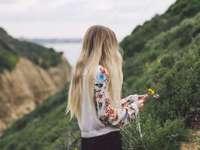 Blondynka zbiera kwiaty - kobieta ubrana w biało-zielono-czerwoną kwiecistą koszulę z długimi rękawami, stojąca na ziel