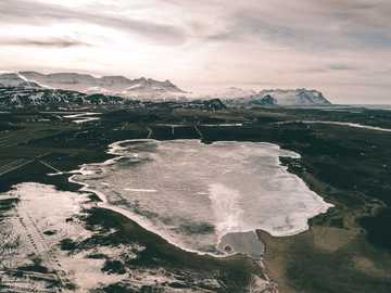 Frozen waters - body of water across white mountains. Reykholt, Iceland