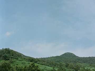 Green mountain range, blue sky - green mountain under white clouds during daytime.