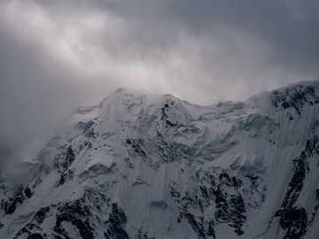 Връх Нанга Парбат под облаци - заснежена планина под облачно небе. Нанга Парбат