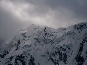 Nanga Parbat Peak under clouds - snow covered mountain under cloudy sky. Nanga Parbat