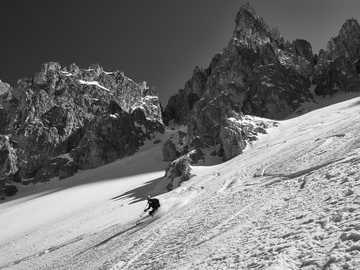 osoba, jízda na sněhu na lyžích ve stupních šedi - V neobvyklém údolí Odles v Dolomitech, daleko od lyžařských středisek.