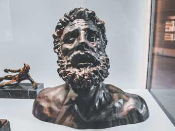 man sculpture - black skull figurine on white table.