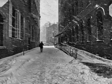 Ztracen v Soho - ve stupních šedi fotografie osoby, která kráčí po zasněžené silnici. New York, Spojené st�