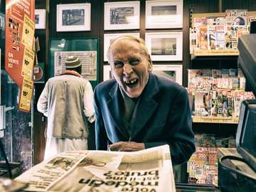 man in black suit jacket while smiling - Série sur une journée dans la vie d'un buraliste.