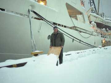 uomo in piedi sulla neve vicino alla barca durante il giorno - Tempesta di neve a Seattle. Utilizzo di un metodo improvvisato per pulire la neve sul molo.