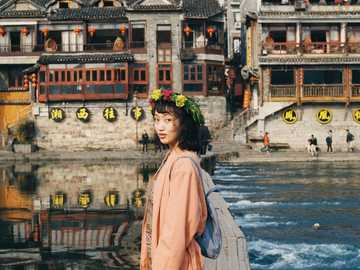 Flowers girl! - woman in pink dress standing in front of lake near temples. Fenghuang, Xiangxi, China