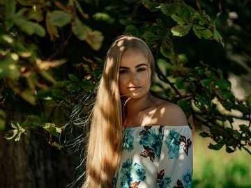 Dívka v přírodě - žena v modré a bílé květinové špagety popruh nahoře stojící poblíž zelené listy. Djurg�