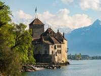 Chillon Castle at lake Geneva in Switzerland - gray concrete building near mountain during daytime.