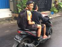 Children of the World. Going home from school. - man in black and yellow polo shirt riding on black and red motorcycle during daytime. Bali, Indonesi