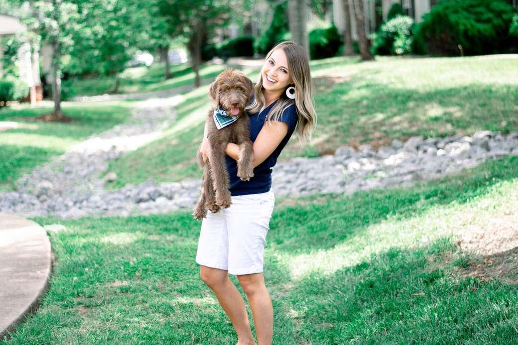 Dívka drží štěně, zatímco s úsměvem. - žena v bílém tílku nesoucí plyšovou hračku medvěda hnědého. Murfreesboro, TN, USA