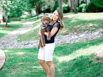 Menina segurando o cachorrinho enquanto sorri. - mulher em um top branco carregando um brinquedo de pelúcia urso marrom Murfreesboro, TN, EUA