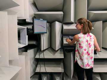 Female noise and vibration engineer collects sound data in anechoic chamber - woman in white pink and green floral shirt standing beside gray flat screen tv.
