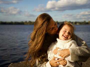 Mutter und Tochter lächeln - Frau im weißen Pullover trägt Mädchen im weißen Pullover.