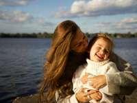 Mama și fiica zâmbind - femeie în pulover alb care poartă fată în pulover alb.