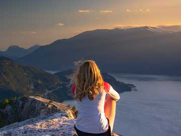 Mulher sentada no topo da montanha ao pôr do sol. - mulher de camiseta branca sentada na formação rochosa perto do corpo d'água durante o dia. S