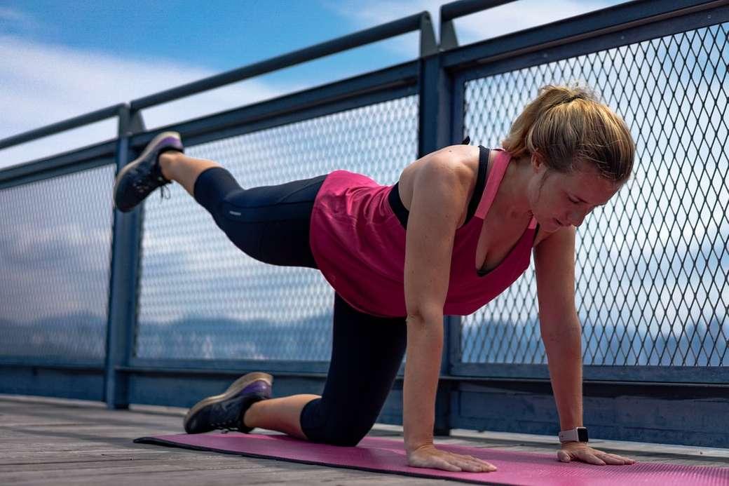 mulher de blusa vermelha e legging preta fazendo ioga