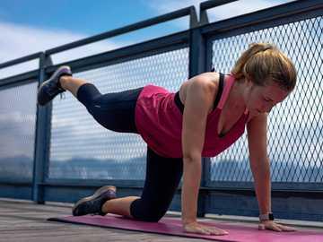 Frau im roten Trägershirt und in den schwarzen Leggings, die Yoga tun