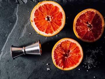 Grapefruit - šedý pohár a pomeranče.