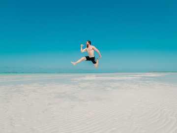 Скок на SandBar - снимка на времето на човек, скачащ на морския бряг.