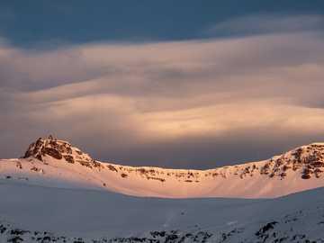 Zima na Islandu. - zasněžená hora pod zamračenou oblohou během dne. Seyðisfjörður