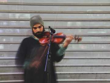 равномерни движения - човек, който свири на цигулка през деня. Търговски цент
