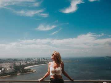 Travel, blond woman chill - woman in white bikini standing on the edge of a building looking at the sea during. Rio de Janeiro,