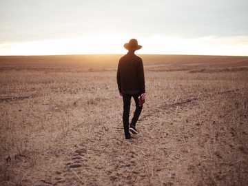 Veldwandelingen - man loopt op gedroogde vlakte terwijl hij naar de zon aan de horizon kijkt. Three Hills, Canada