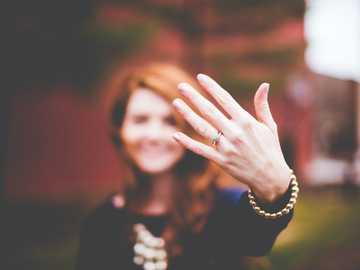 Afișaj inel de logodnă - femeie care prezintă inel de culoare argintie.
