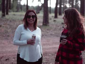 kvinna i vit tröja som håller vit keramisk mugg - Vänner som campar, flanell, i skogen, dricker öl. West Clear Creek Canyon, Camp Verde, AZ, USA