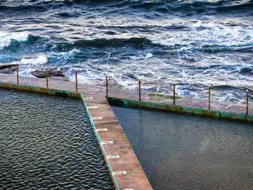 Piscina de pedras - doca marrom perto de corpo d'água durante o dia. Collaroy Beach, Austrália