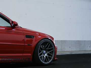 BMW M3 E46 - red car parked beside white wall. Schweiz