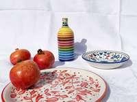 червени ябълки върху бяла и синя флорална керамична чиния