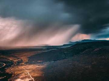 bruine en zwarte bergen onder grijze wolken - Naderende regenbui over een berglandschap. Graaff-Reinet, Zuid-Afrika