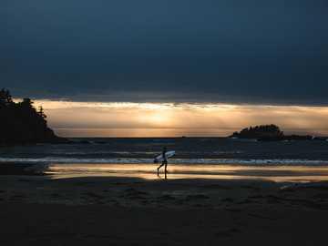 person som håller surfbrädan som går på stranden - Fångad efter lite surfing i Tofino vid solnedgången. Tofino, Kanada