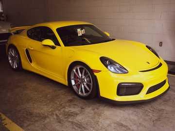 Porsche Cayman GT4 - amarelo ferrari 458 italia estacionado na garagem.