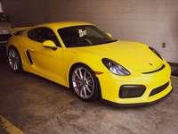 Porsche Cayman GT4 - yellow ferrari 458 italia parked in garage.