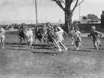 Running Race voor meisjes, circa 1930 - grijswaardenfoto van mensen die op de weg lopen.