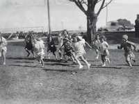 Corrida de corrida para meninas, por volta de 1930 - foto em tons de cinza de pessoas andando na estrada.