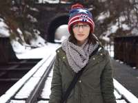 Vrouw op treinsporen - vrouw in groene jas met zwarte draagzak staande op spoorweg. Sykesville, Verenigde Staten