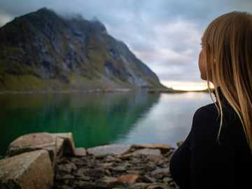 Solo Travel to a Fjord in Norway's Arctic Circle - woman in black jacket sitting on rock near lake during daytime. Lofoten Islands, Gimsøysand, Norway