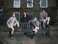 Models in blazers on bench - photography of group of people sitting on bench.
