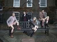 Modellen in blazers op de bank - fotografie van een groep mensen zittend op de bank.
