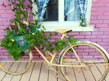 Κίτρινος ποδηλάτης - καφέ πόλη ποδήλατο με λουλούδια κοντά σε τούβλινο κτίρ